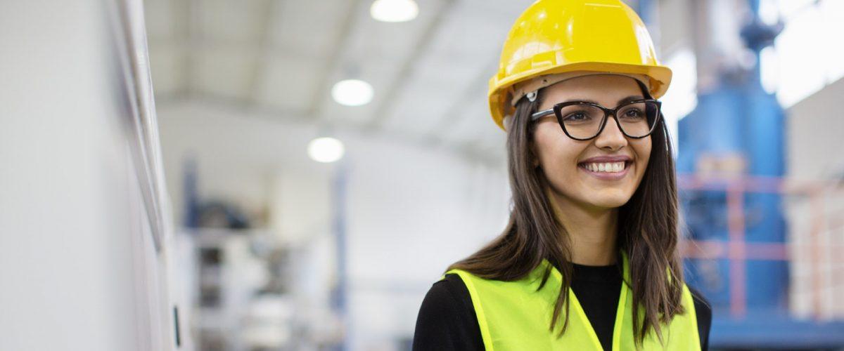 Schönes Mädchen in der Fabrik in einer Weste und einem Helm, das lächelt und einen Händedruck macht.