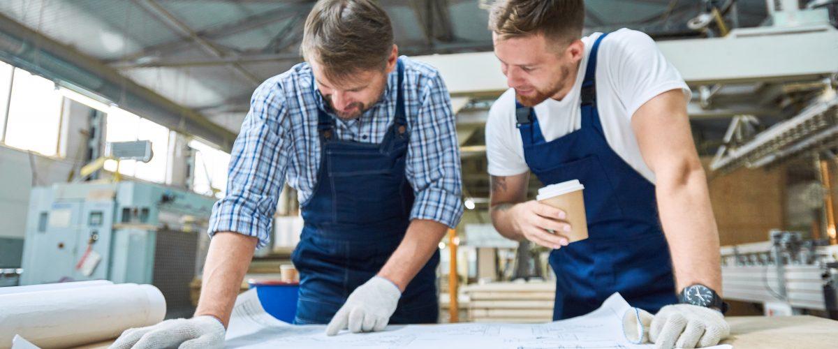 Frontalansicht Porträt zweier Arbeiter, die in der Werkstatt einer modernen Industriefabrik über Projektpläne diskutieren.