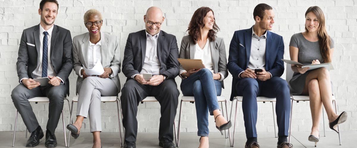 Eine Gruppe von verschiedenen Personen wartet auf ein Vorstellungsgespräch.